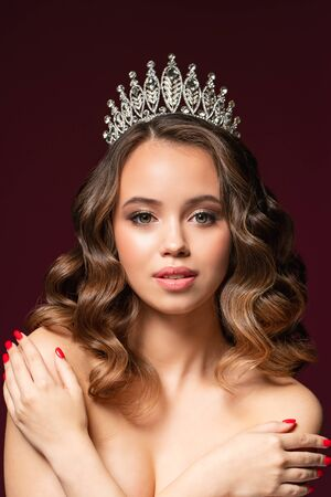 Beautiful portrait of young woman with perfect make-up, hairstyle, and nail design. Beauty contest. Crown on her head. Studio shot