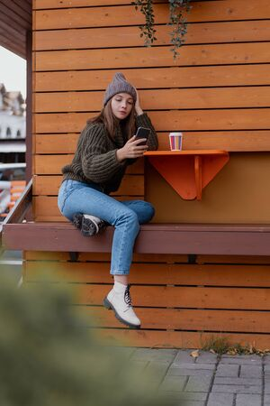 Young woman in hat and sweater sitting on the outdoor cafe, using smartphone, making selfie and drinking coffee. Lifestyle Foto de archivo - 133207101