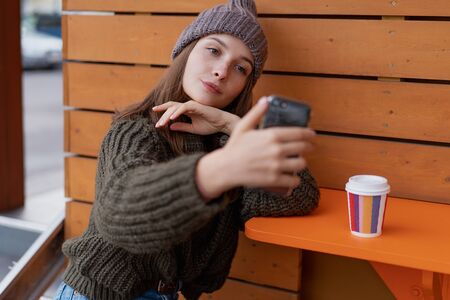 Young woman in hat and sweater sitting on the outdoor cafe, using smartphone, making selfie and drinking coffee. Lifestyle Foto de archivo - 133207108