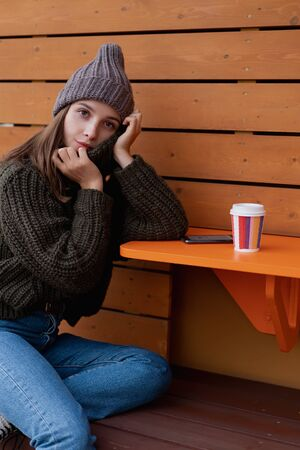 Young woman in hat and sweater sitting on the outdoor cafe, using smartphone, making selfie and drinking coffee. Lifestyle Foto de archivo - 133207117