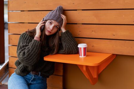 Young woman in hat and sweater sitting on the outdoor cafe, using smartphone, making selfie and drinking coffee. Lifestyle Foto de archivo - 133207120