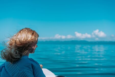 Beautiful blond woman enjoying the sun and water splash, while traveling on the boat. Wind in her hair. Concept Vacation, travel, dream Foto de archivo - 132570490