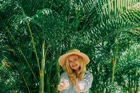 Portrait of beautiful of traveler woman with hat smiling behind palm trees. Sunlight. Concept travel, vacation, dream Foto de archivo - 133207165