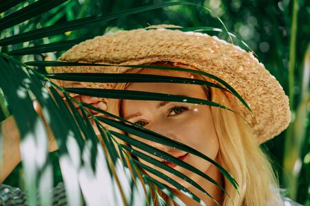Portrait of beautiful of traveler woman with hat smiling behind palm trees. Sunlight. Concept travel, vacation, dream Foto de archivo - 133207182