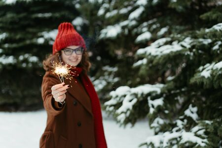 Young beautiful woman in knitted red hat and scarf standing in the park with bengal light, sparkler. Concept celebration, christmas. Winter Foto de archivo - 133208873