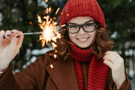 Young beautiful woman in knitted red hat and scarf standing in the park with bengal light, sparkler. Concept celebration, christmas. Winter Foto de archivo - 133208885