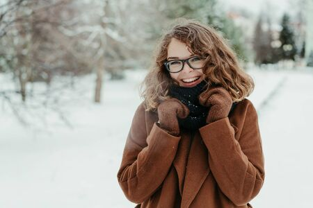 Young beautiful hipster woman in knitted scarf standing in the park and smiling. Winter fashion. Snow Foto de archivo - 133208917