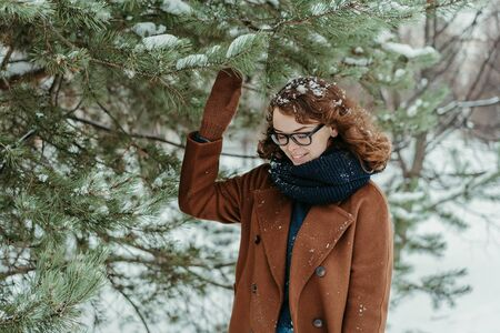 Young beautiful hipster woman in knitted scarf standing in the park and smiling. Winter fashion. Snow Foto de archivo - 133208920