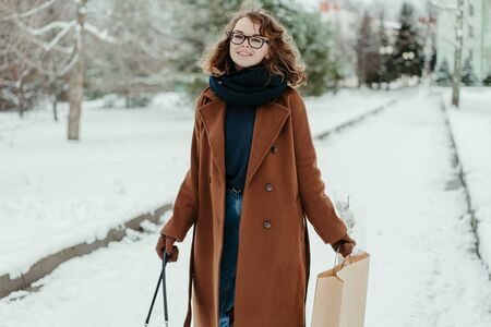 Young beautiful woman in knitted scarf standing in the park with shopping bag. Winter fashion Foto de archivo - 133209123