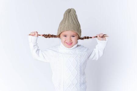 Little girl in knitted sweater and hat posing in studio. Winter fashion. Isolated Foto de archivo - 133209127