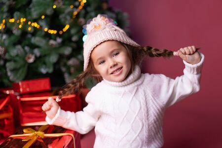 Beautiful little girl in the hat sitting near presents and christmas tree. Bokeh lights on the background. Concept christmas and new year Foto de archivo - 133209133