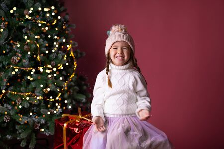 Beautiful little girl in the hat sitting near presents and christmas tree. Bokeh lights on the background. Concept christmas and new year Foto de archivo - 133179107