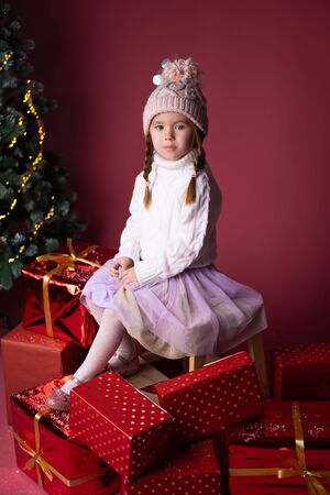 Beautiful little girl in the hat sitting near presents and christmas tree. Bokeh lights on the background. Concept christmas and new year Foto de archivo - 133178906