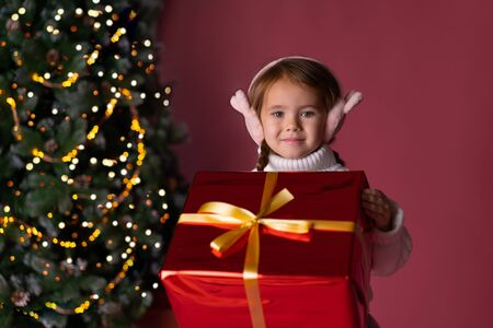 Beautiful little girl in the hat sitting near presents and christmas tree. Bokeh lights on the background. Concept christmas and new year Foto de archivo - 133209136