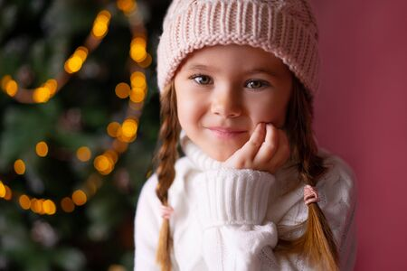 Beautiful little girl in the hat sitting near presents and christmas tree. Bokeh lights on the background. Concept christmas and new year Foto de archivo - 133209144