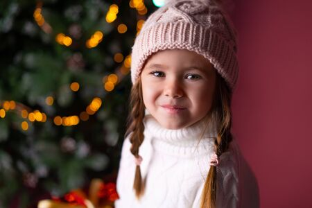 Beautiful little girl in the hat sitting near presents and christmas tree. Bokeh lights on the background. Concept christmas and new year Foto de archivo - 133209148