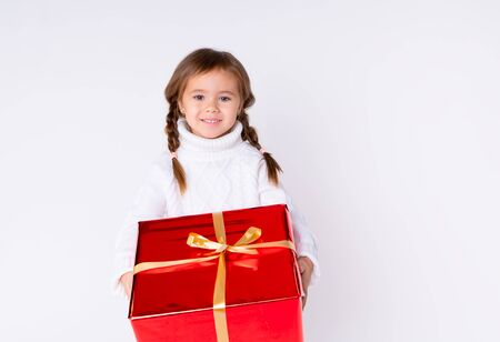 little cute girl in knitted white sweater holding a present in studio. Concept Christmas, New Year, Birthday. Isolated Foto de archivo - 133209150