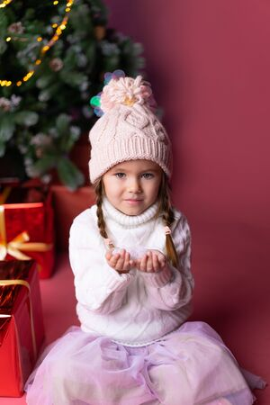 Beautiful little girl in the hat playing with snow near presents and christmas tree. Bokeh lights on the background. Concept christmas and new year Foto de archivo - 133181064