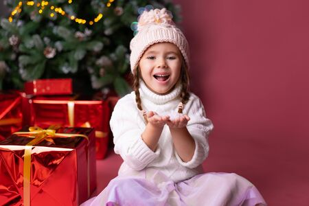 Beautiful little girl in the hat playing with snow near presents and christmas tree. Bokeh lights on the background. Concept christmas and new year Foto de archivo - 133184176