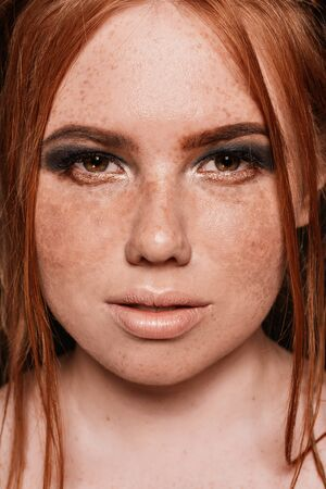 Close-up portrait of beautiful natural woman with freckles on her face and blue glittered smokey eyes make-up. Red hairstyle. Studio