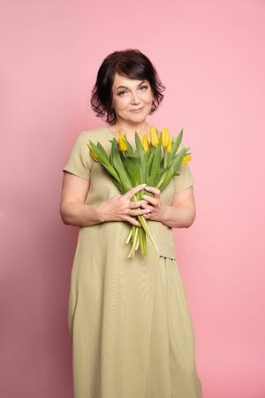 Beautiful old woman with professional smokey make-up and hairstyle holding tulip flowers on the pink background. Concept spring, mothers day