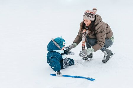 Little funny boy skating in the park and fell with his mother. Learn to Play ice hockey with stick. Outdoor. Winter sport. Lifestyle