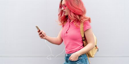 Beautiful woman with colored pink hairs, wireless headphones and smartphone over grey background. Banner
