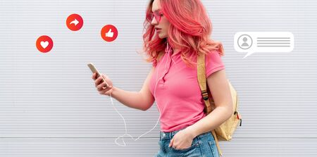 Beautiful woman with colored pink hairs, wireless headphones and smartphone over grey background. Banner. Smm icons Stock fotó
