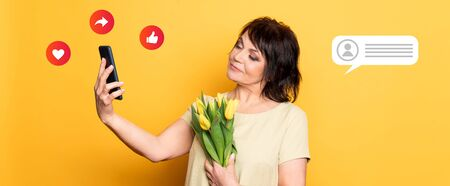 Beautiful old woman with professional smokey make-up and hairstyle holding tulip flowers on the pink background. Taking video call by the smartphone . Smm and icons