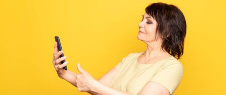 Beautiful senior woman with professional smokey make-up and hairstyle holding cellphone on the yellow background. Taking videocall by the smartphone 스톡 콘텐츠