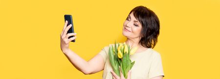 Beautiful old woman with professional smokey make-up and hairstyle holding tulip flowers on the yellow background. Taking videocall by the smartphone 스톡 콘텐츠