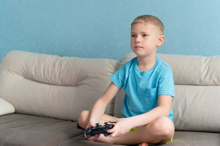 Little cute boy in blue t-shirt play with joystick in electronic game in his room