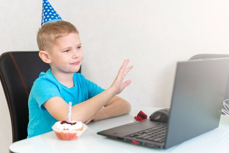 Little boy in festive cap talking online with his relatives and friends by notebook. Concept online birthday. Holiday