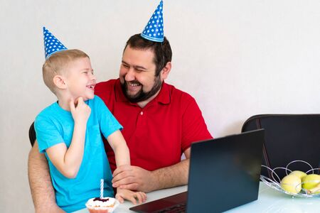 Little boy with his father celebrate birthday online, talking by notebook with relatives and friends.