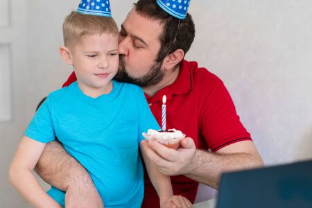 Little boy with his father celebrate birthday online, talking by notebook with relatives and friends. Blow out the candle on the cake