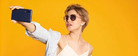 Fashion portrait of pretty woman in sunglasses with smartphone against the colorful orange wall. Copyspace 스톡 콘텐츠