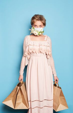Fashion beauty cool young girl in medical mask designed with natural flowers standing with shopping bags in summer dress over colorful blue background 스톡 콘텐츠