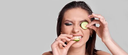 Concept Face care at home. Portrait of young beautiful woman with cucumber on her face. Banner 스톡 콘텐츠