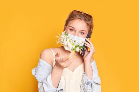 Beautiful woman in medical mask with flower design, holding telephone. Orange background