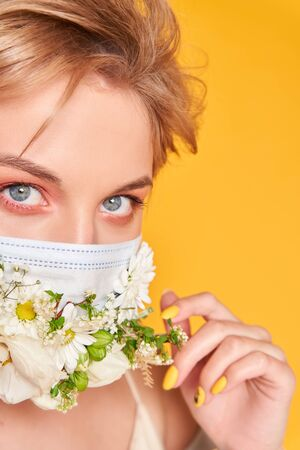 Face mask design with flowers. Portrait of beautiful woman with blue eyes, fashion make-up and mask over orange background