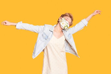 Beautiful woman in medical mask with flower design dancing and enjoying life on the orange background