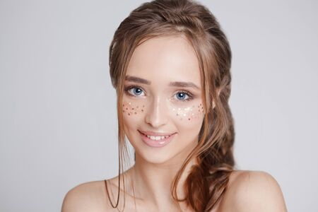 youth women with glitter freckles on the face, beautiful hairstyle. grey background