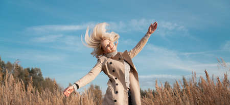 Flying hairs. Young woman jumping on the field, autumn clothes. Action