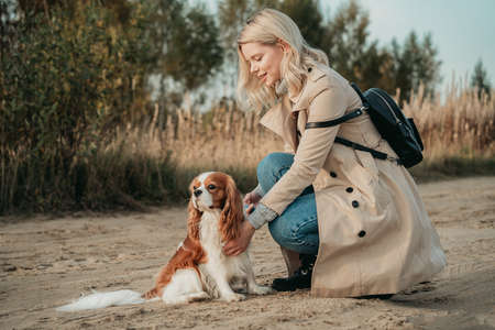 Travel with dog. Young woman walk with her cocker spaniel, backpack on her shoulder.