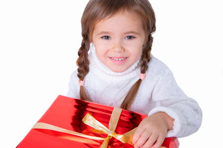 Beautiful little girl in sweater holding christmas present. Concept christmas and new year 스톡 콘텐츠