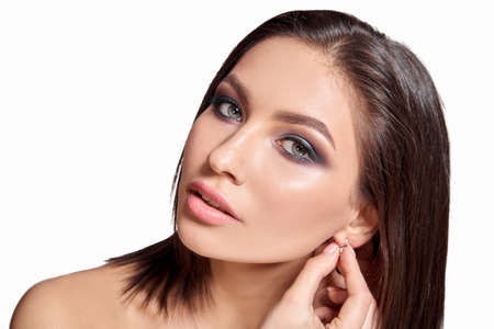 Cosmetology. Portrait of beautiful woman with Fresh Skin and smokey eyes make-up. Isolated