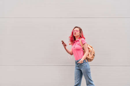Young blogger woman with pink dyed hairs staying near the grey wall and using smartphone. Outdoor