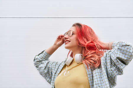 Young hipster woman with dyed pink hairstyle, wireless headphones and sunglasses smiling on the grey background. 스톡 콘텐츠