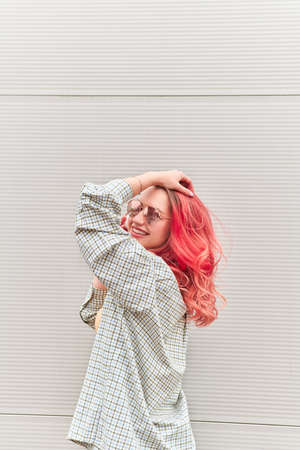 Young hipster woman with dyed pink hairstyle and sunglasses smiling on the grey background.