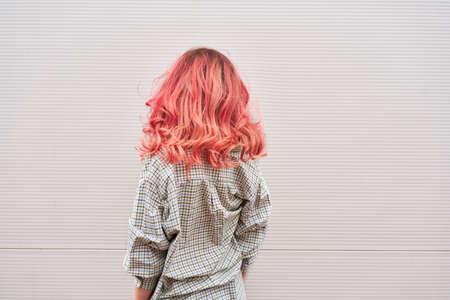 Womans back with dyed pink hairstyle, gray wall background 스톡 콘텐츠